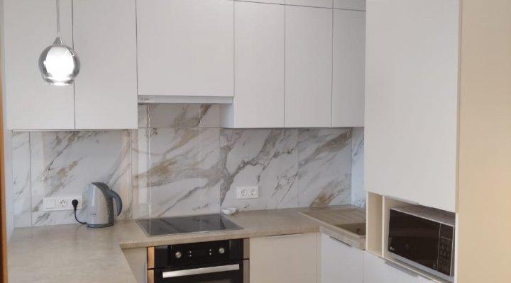 Светлая матовая кухня под потолок с пеналами и барной стойкой