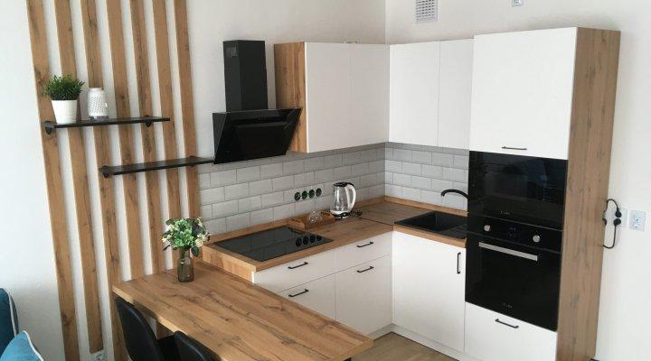 Белая кухня с корпусами, декоративными рейками и столешницей под дерево