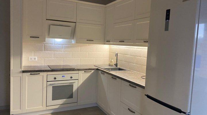 Кухня с белыми стильными фасадами под классику с пеналами