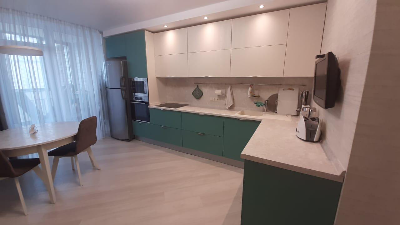 Первое фото Стильная зеленая кухня со светлыми верхними фасадами