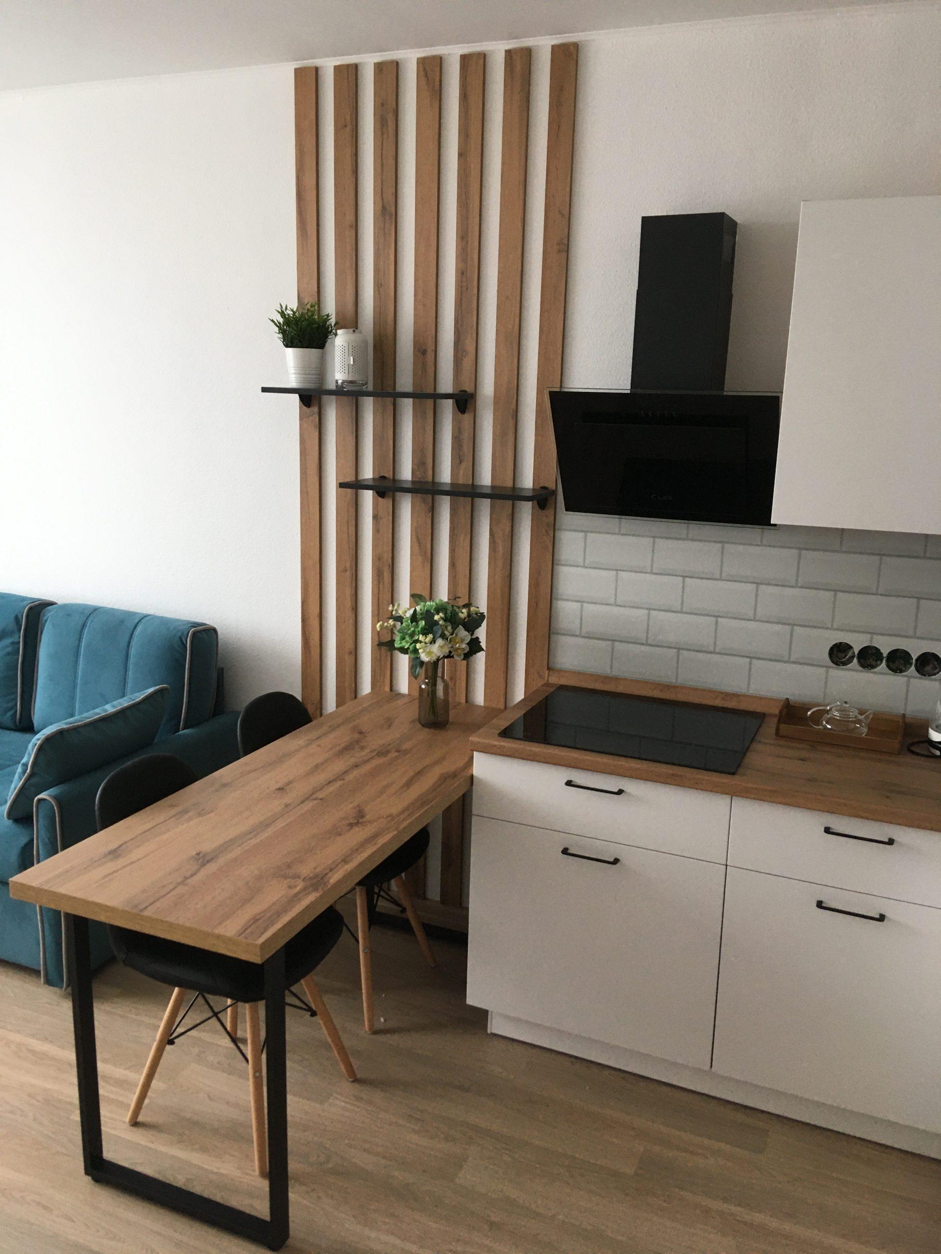 Третье фото Белая кухня с корпусами, декоративными рейками и столешницей под дерево