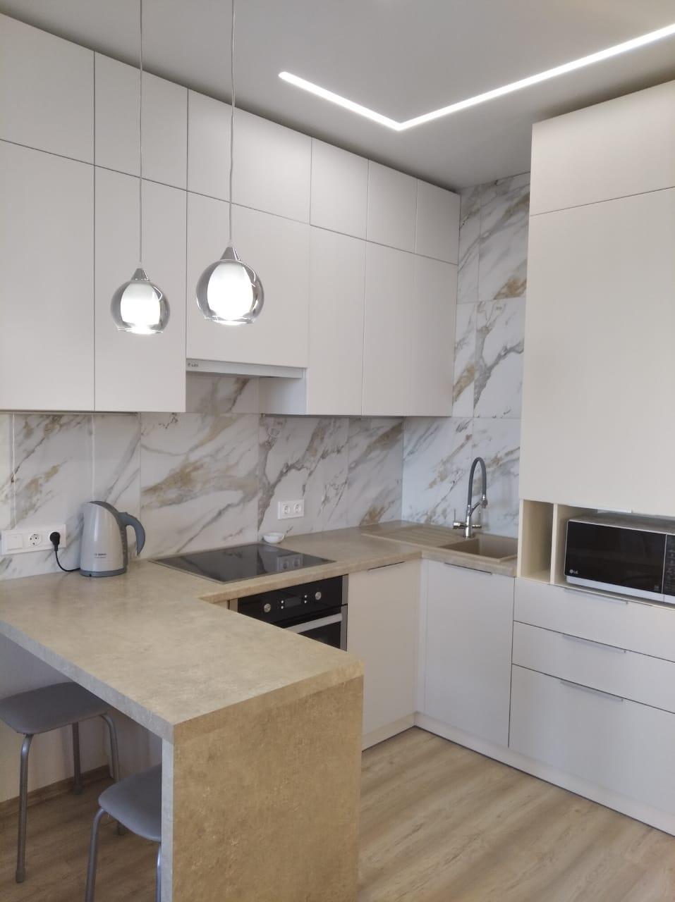 Первое фото Светлая матовая кухня под потолок с пеналами и барной стойкой